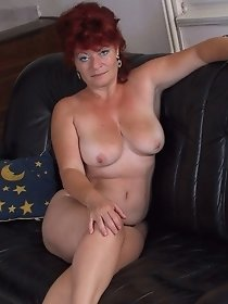 Sexy redhead babe on the black couch